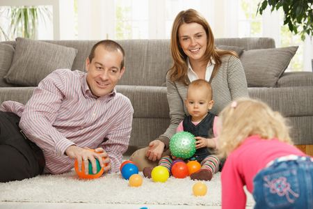 Smiling family of four playing with balls on living room floor. photo
