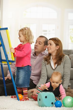 Parents watching toddler girl drawing on board, baby girl playing on floor. Stock Photo - 6374528