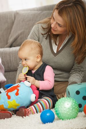 Mother sitting with baby girl on floor surrounded by toys at home. photo