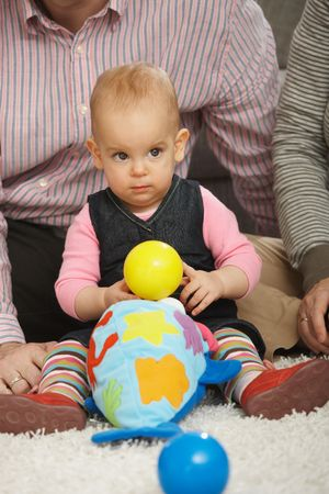 Baby girl sitting on floor holding ball playing with toys. photo