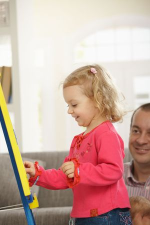 Smiling toddler drawing on board, dad watching in background of living room. photo
