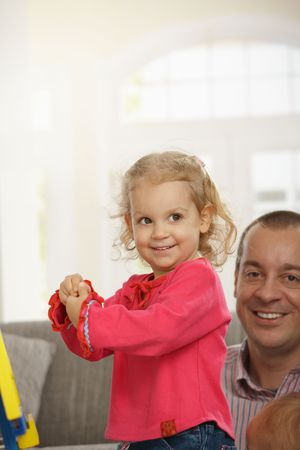 Smiling toddler at home, dad watching in background of living room. Stock Photo - 6374422