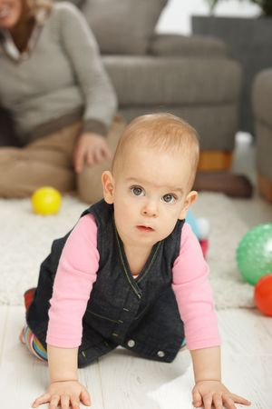 Portrait of cute baby girl kneeling on living room floor looking aside. Stock Photo - 6374417
