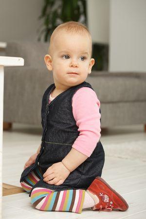 Portrait of cute baby girl kneeling on living room floor looking aside. Stock Photo - 6374433