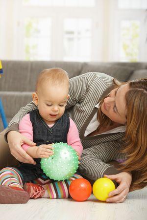 Baby girl smiling holding ball in hands, mum cuddling baby. photo
