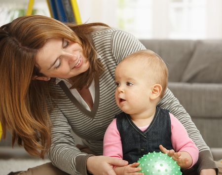 Smiling mother playing with little girl holding ball at home. Stock Photo - 6374488