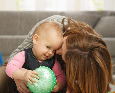 Baby girl smiling holding ball in hands, mum cuddling kissing baby on cheek. photo