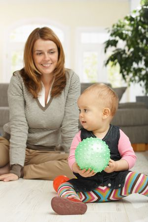 Little girl playing with ball sitting on living room floor, mum in background looking happy. Stock Photo - 6374456