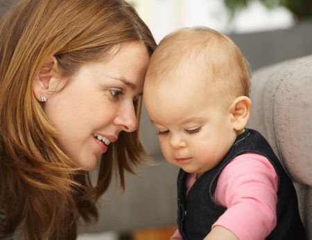 Smiling mother leaning close to baby girl in closeup. Stock Photo - 6374500