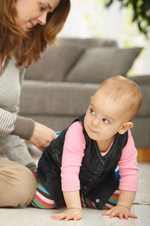 Baby girl crawling on floor with mum sitting in the background. Stock Photo - 6374519