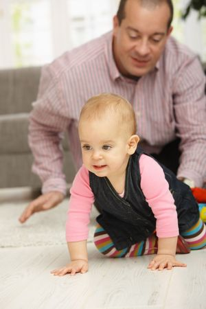 Baby girl crawling on floor, dad watching in background smiling. Stock Photo - 6374427