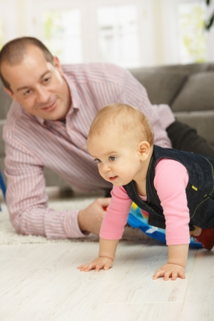 Baby girl crawling on floor, dad watching in background smiling. Stock Photo - 6374415