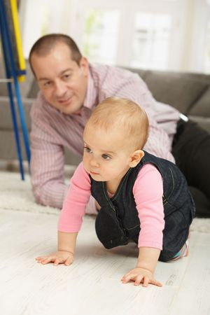 Baby girl crawling on floor, dad watching in background smiling. photo