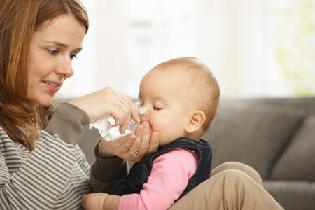Happy mum holding baby girl in arms smiling baby drinking from feeding bottle. photo