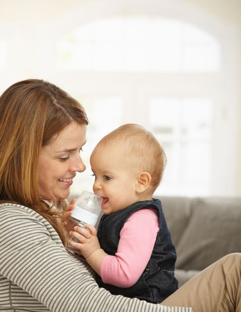 Happy mum holding baby girl in arms smiling. Stock Photo - 6374501
