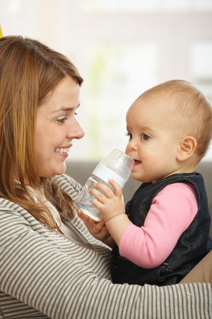 Happy mum holding baby girl in arms smiling. Stock Photo - 6374472