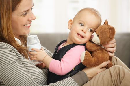 tenderly: Happy mum and baby girl laughing cuddling holding teddy bear. Stock Photo