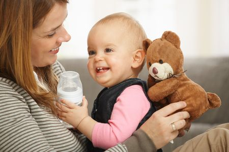 Happy mum and baby girl laughing cuddling holding teddy bear. Stock Photo - 6374548