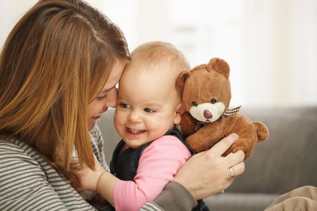 Happy mum and baby girl laughing cuddling holding teddy bear. photo