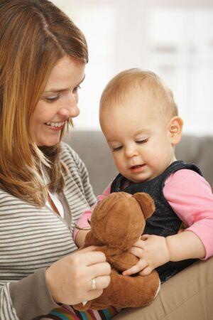 Happy mum and baby girl cuddling holding teddy bear. photo