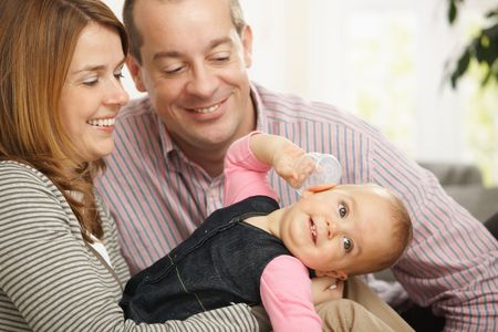 Smiling baby girl held by happy mother, father sitting smiling down at baby at home. Stock Photo - 6374557