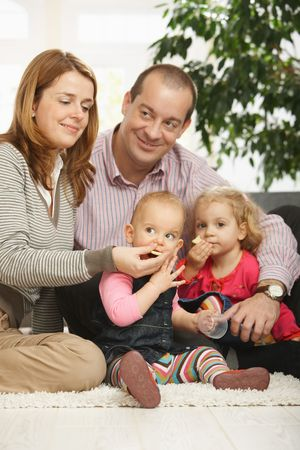 Portrait of happy family with two daughters sitting together on living room floor. photo