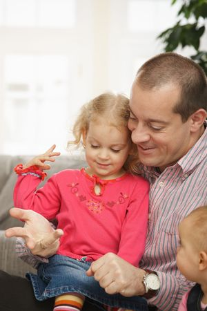 Smiling father sitting with small daughters talking playing at home. photo