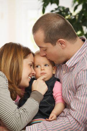 tenderly: Bambina dormire nel braccio del padre sul divano, padre baciare sulla testa, madre guardando con tenerezza.
