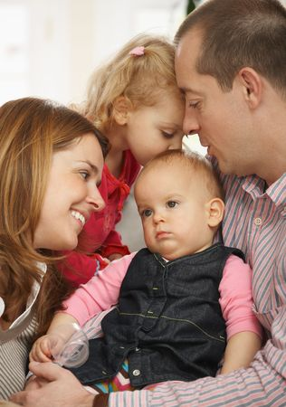 sibling: Happy family portrait, dad holding sleepy baby girl,mum smiling and toddler kissing babys head.