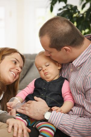 Baby girl sleeping in father's arm on sofa, father kissing on head, mother looking tenderly. Stock Photo - 6374552