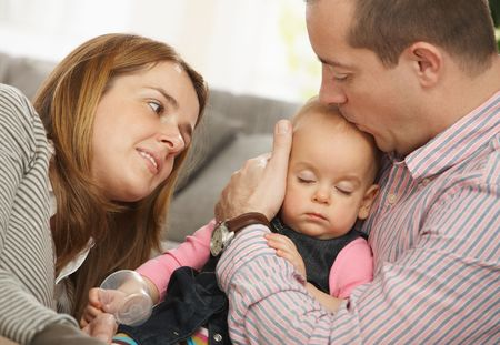Baby girl sleeping in father's arm on sofa, father kissing on head, mother looking tenderly. Stock Photo - 6374549