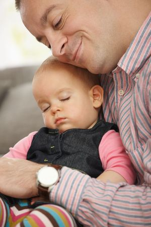 effortless: Cute little baby sleeping held in fathers arm at home. Stock Photo