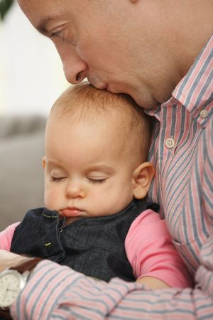 Cute little baby sleeping held in fathers arm at home, father kissing baby. photo