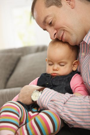 Cute little baby sleeping held in father's arm at home. Stock Photo - 6374507