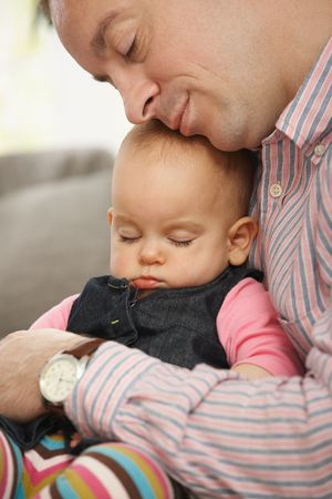 Cute little baby sleeping held in father's arm at home. Stock Photo - 6374478