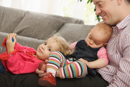 Happy dad sitting with smiling toddler and sleeping baby in lap at home. Stock Photo - 6374489