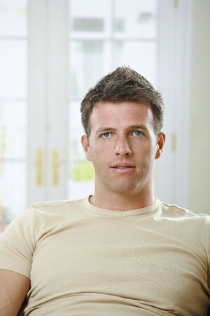 Portrait of mid-adult man sitting at home in front of window in causal t-shirt. Stock Photo - 6396964