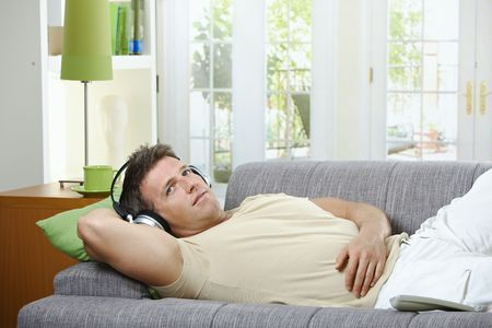 Handsome man with smile listening to music on headphones lying on couch. photo