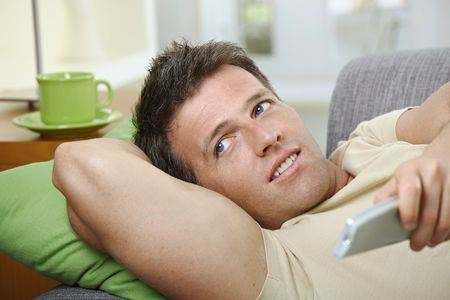 Goodlooking man in causal wear smiling on sofa using remote control. Stock Photo - 6397075