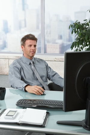 involved: Successful mid-adult businessman dealing with computer tasks sitting at desk in office. Stock Photo