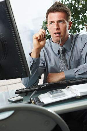 Confident businessman focusing on computer screen sitting at desk in office. Stock Photo - 6397026