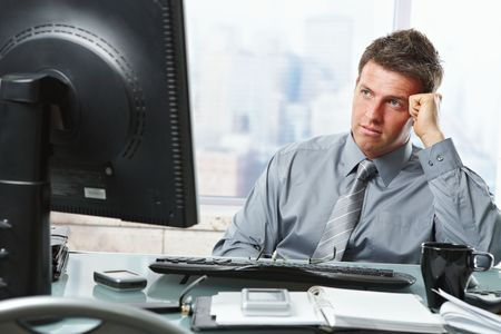 Mid-adult businessman making difficult decision looking at screen in office. photo