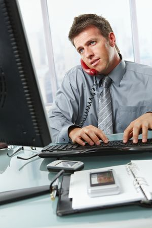 handheld computer: Businessman at office desk busy with typing on keyboard, talking on landline phone and looking at screen.
