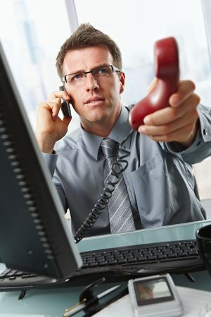 answer phone: Businessman with glasses busy talking on mobile phone handing over landline call to answer in office. Stock Photo