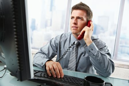 involved: Determined businessman discussing computer work on landline phone while looking at screen typing on keyboard at office desk.