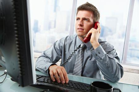 hablando por telefono: Empresario determinado discutir el trabajo de equipo en el tel�fono de l�nea fija mirando la pantalla escribiendo en teclado en mostrador de la Oficina.