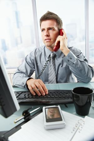 Determined businessman discussing computer work on landline phone while looking at screen typing on keyboard at office desk. Stock Photo - 6397031