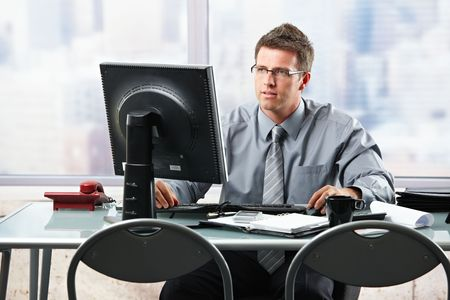 involved: Determined businessman working on computer project looking at screen in skyscraper office. Stock Photo