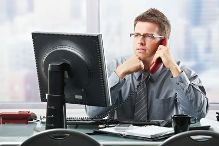 focused: Focused businessman listening to explanation of computer report on landline phone looking at screen sitting in office.