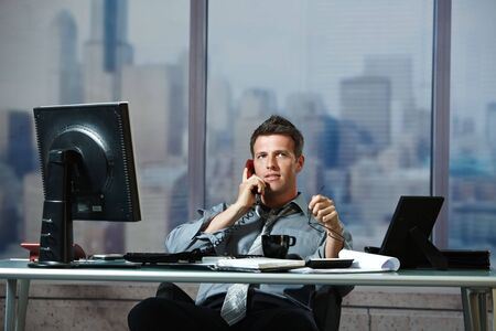 Mid-adult successful smiling businessman calling on landline listening to conversation sitting at office desk. Stock Photo - 6397016